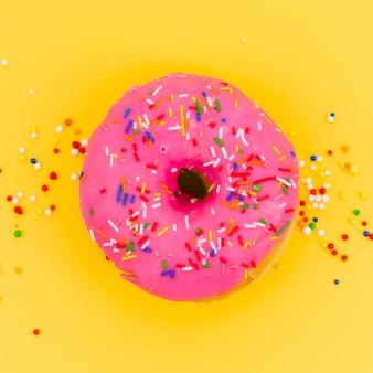 黄色の背景にピンクのドーナツに振りかける