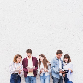 Молодые люди стоят и читают книги, обсуждая содержание