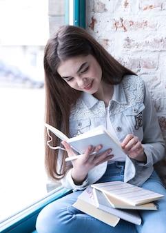 Девушка подростка сидя с открытой книгой и усмехаясь пока читающ ее