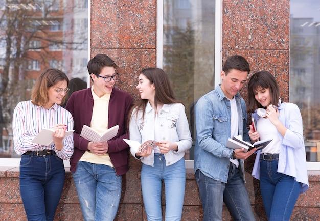 Молодые люди стоят с книгами и читают их, обсуждая содержание