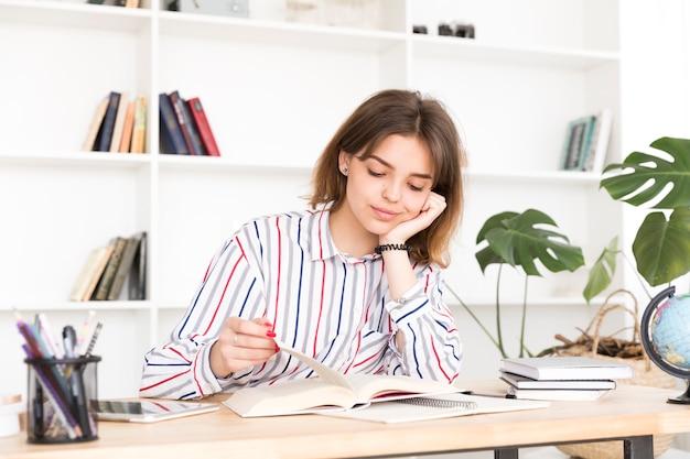 女子学生の木製の机で読書