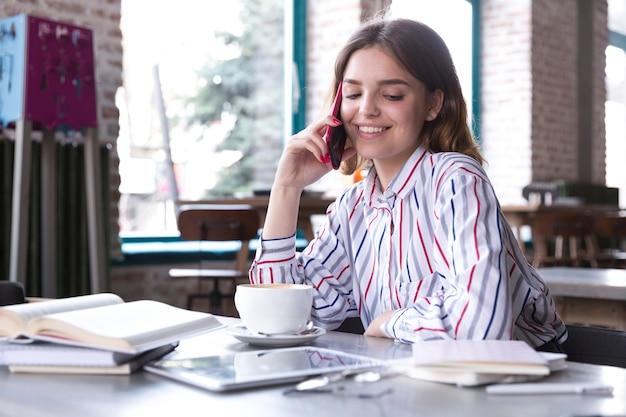 スマートフォンで話している女性の笑みを浮かべてください。