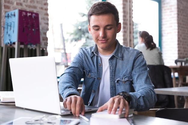 ノートパソコンを持つテーブルで若い男