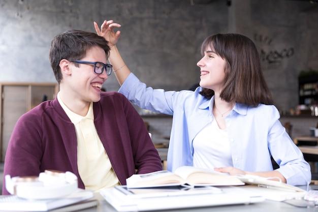 Студенты-подростки сидят за столом и веселятся