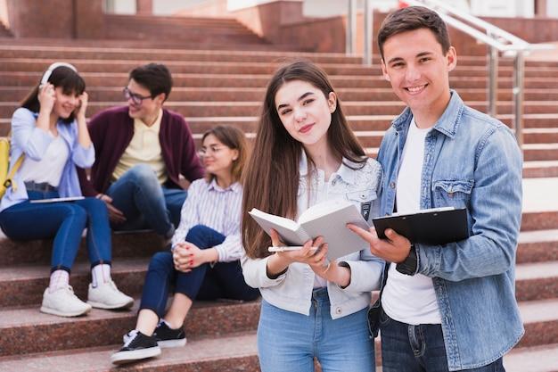 Студенты стоят с открытыми книгами и смотрят в камеру