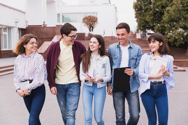 Студенты-подростки смеются и гуляют с книгами
