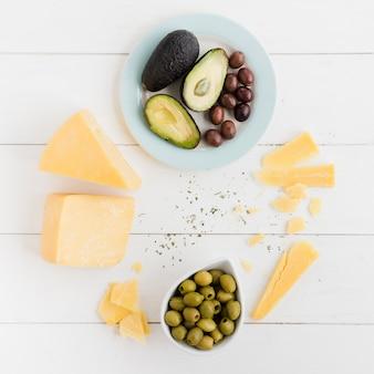 アボカドの俯瞰図。オリーブと白いテーブルの上のチーズの塊