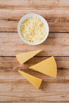 Тертый и треугольный сыр на деревянном столе