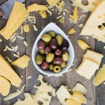 木製のテーブルの上のオリーブボウルの近くに広がるチーズ