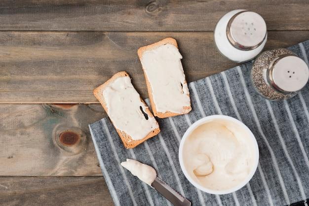 木製のテーブルに塩とコショウのシェーカーでトーストのパンに広がるチーズ