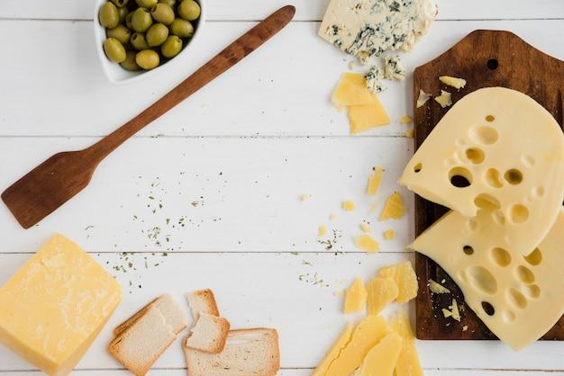オリーブとパンのスライス。パンと白い机の上のチーズ