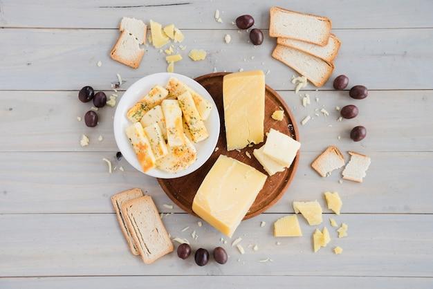 パン;テーブルの上の朝食のためのチーズの塊とオリーブ