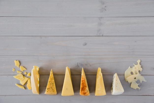 灰色の木製の机の上の三角チーズの行