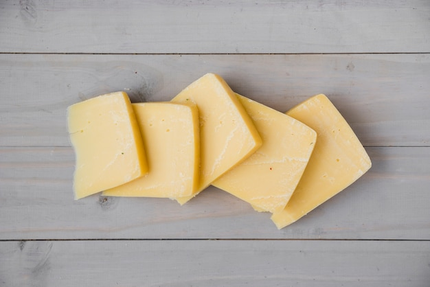木製の机の上の新鮮なゴーダチーズスライスの立面図