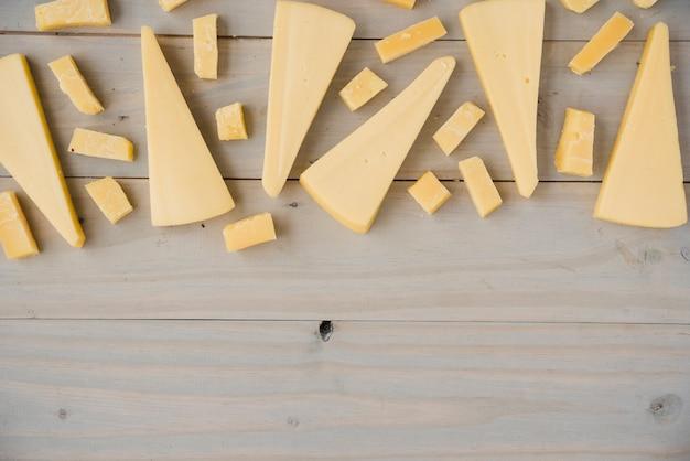 木製のテーブルにさまざまな形のチェダーチーズの種類