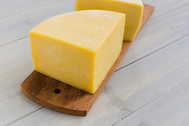 机の上の木製のまな板にイタリアンチーズ