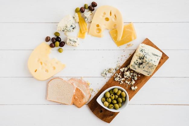 白いテーブルの上のパンとオリーブのおいしいチーズ各種