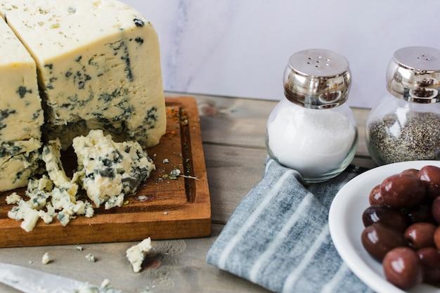 Голубой сыр с оливками; шейкер с солью и черным перцем с салфеткой на деревянный стол