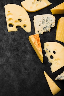 ウェッジと黒キッチンのワークトップにチーズのスライス