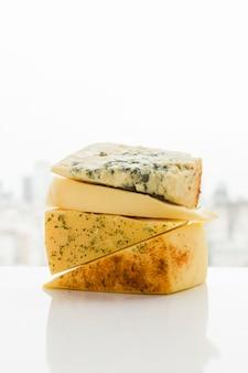 白い机の上のハーブと三角チーズのくさびの種類