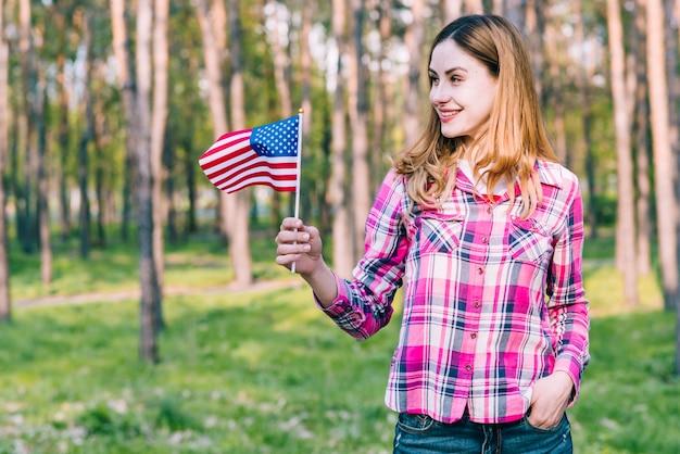 Веселая женщина стоит с американским флагом