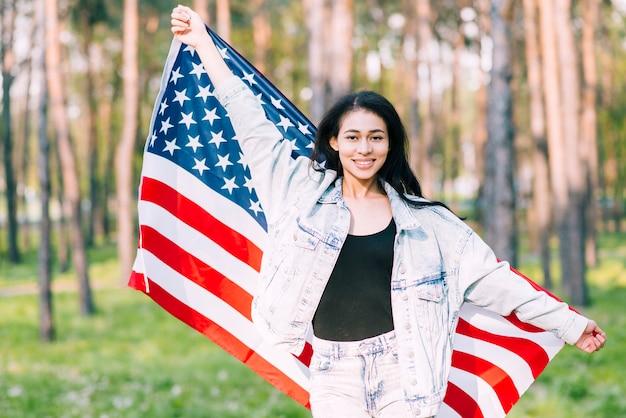 独立記念日に自然の中でアメリカの国旗を振っている若い女性