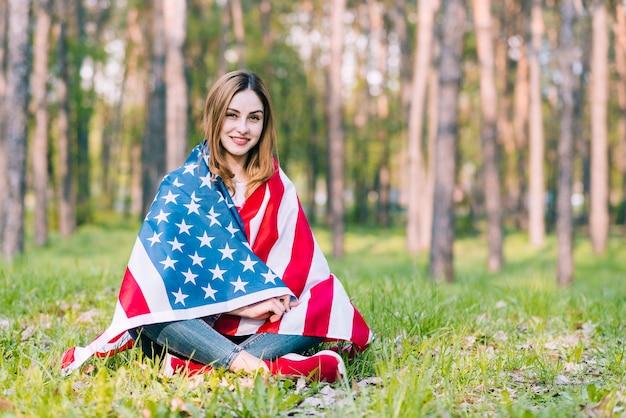 アメリカの国旗を包む地面に座っている若い女性