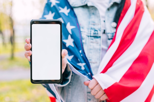 Женщина в американском флаге держит мобильный телефон