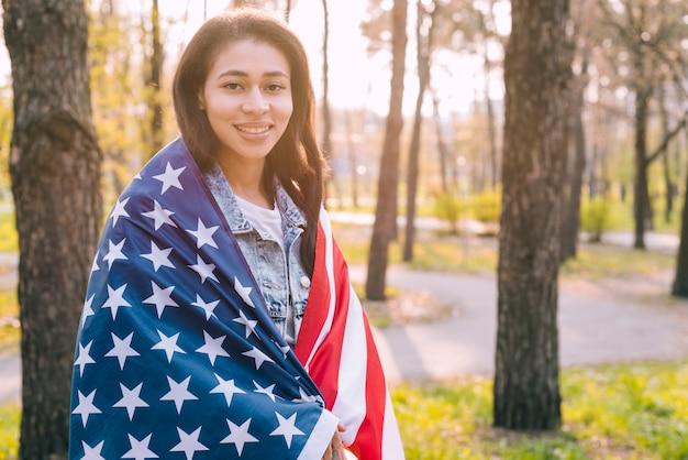 自然の中でアメリカの国旗を包む若い女性