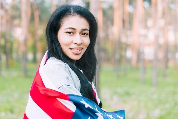 アメリカの国旗を持つ公園で若い女性