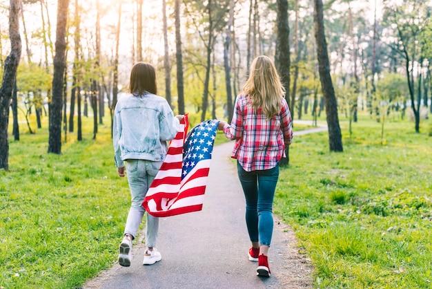 アメリカの国旗と公園を歩いている女性