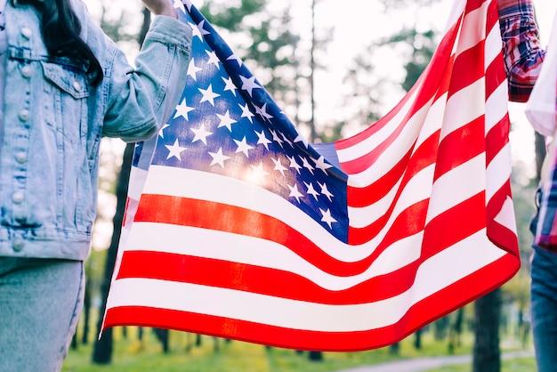 公園でアメリカの国旗を持っている人
