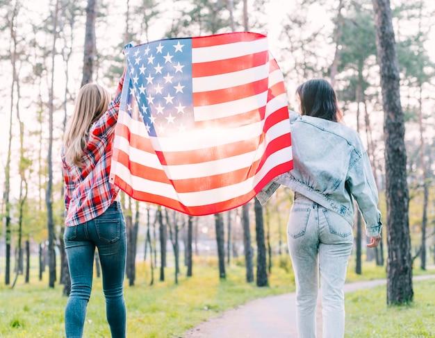 アメリカの国旗を屋外に保持している女子学生