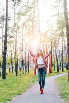 日差しの中でアメリカ国旗を持つ女子学生