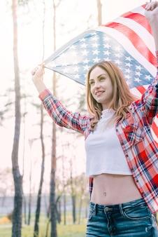 Молодая красивая женщина, размахивая флагом сша