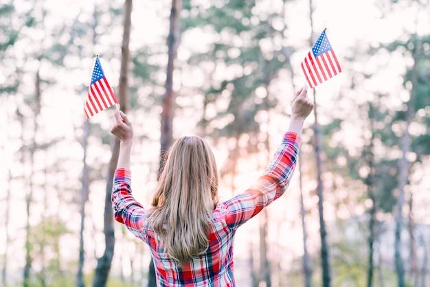 屋外の小さなアメリカの国旗を振っている女性