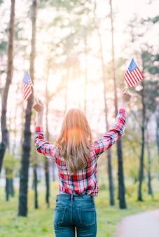 Безликая женщина с флагами сша в лучах солнца