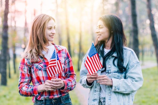 屋外に立っている小さなアメリカの国旗を持つ女性