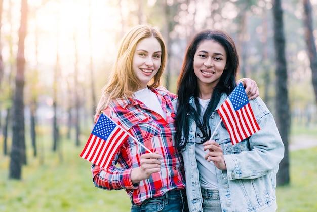 屋外に立っている小さなアメリカの国旗を持つガールフレンド