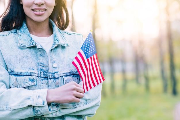 Женщина с маленьким американским флагом на открытом воздухе