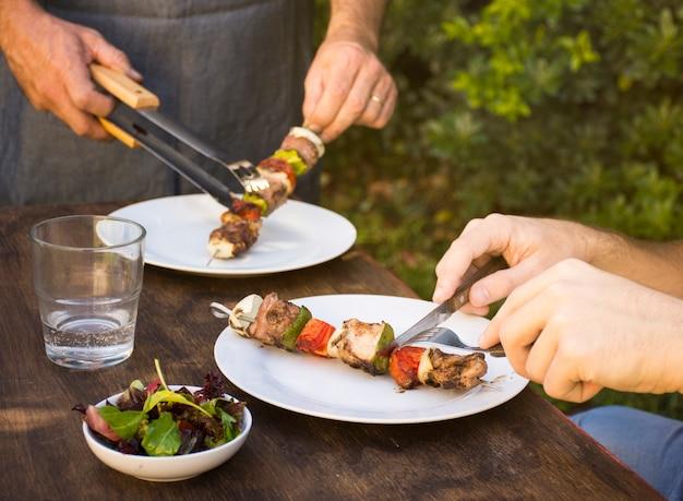 Люди едят приготовленное барбекю в тарелках на столе