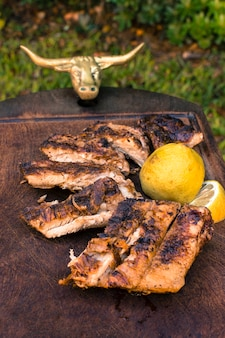 カット肉のグリルとテーブルの上のレモンスライス