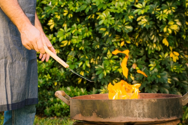 Мужчина разжигает гриль во дворе