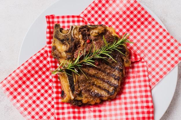 ローズマリーと皿の上のステーキ
