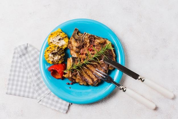 カトラリーと皿の上の野菜とステーキ
