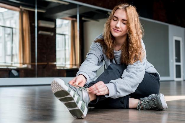 靴ひもを結ぶ床の上に座っている金髪の若い女性