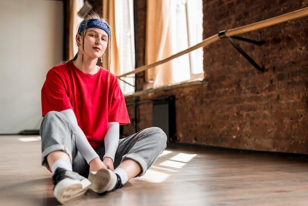 Молодая танцовщица сидит на полу, принимая перерыв от танца