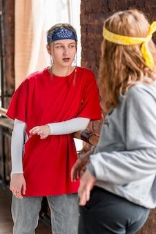 Две танцовщицы стоят в танцевальной студии и разговаривают друг с другом