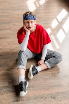 堅い床に座っている思いやりのある若い女性ダンサーの立面図
