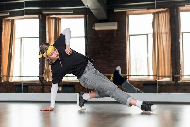 スタジオでダンスを練習するスタイリッシュな若い女性の肖像画